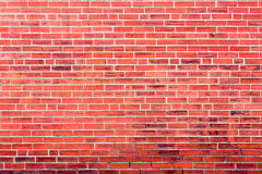 Bright red brick wall background with dark stains Royalty Free Stock Photography