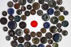 Hostile environment. A bright red button for clothes among other black, dark buttons. Confrontation, loneliness, violation of rules and dress code. White royalty free stock images