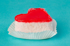 Bright red cake in the form of heart. Bright cake in the form of heart on a blue background Royalty Free Stock Photos