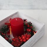 Red candles in a gift box with a Christmas wreath on a white bac. Bright red candle in a white gift box wrapped with a Christmas wreath on a white background stock photos