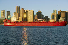 Bright red cargo ship travels in front of Boston Harbor and the Boston skyline at sunrise as seen from South Boston, Massachusetts Royalty Free Stock Photo