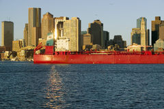 Bright red cargo ship travels in front of Boston Harbor and the Boston skyline at sunrise as seen from South Boston, Massachusetts Royalty Free Stock Images