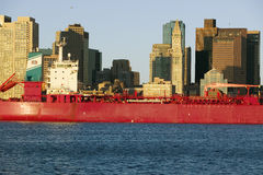 Bright red cargo ship travels in front of Boston Harbor and the Boston skyline at sunrise as seen from South Boston, Massachusetts Royalty Free Stock Photos