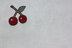 Bright red cherries painted on white wall stock photography