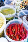 Bright red chilis and North African preserves in white buckets in a French market in Paris Royalty Free Stock Images