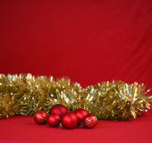 Bright Red Christmas baubles with gold tinsel. Red Christmas baubles with gold tinsel with copy space Stock Image