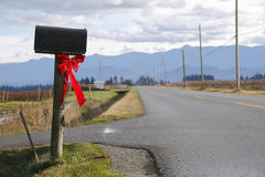 Bright Red Christmas Bow on Rural Mailbox Royalty Free Stock Photography