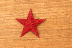 Bright red Christmas star on a wooden background. With copyspace stock image