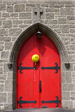 Bright Red Church Door With Happy Balloon. A bright yellow happy face balloon floats in front of a bright red church door Stock Photography