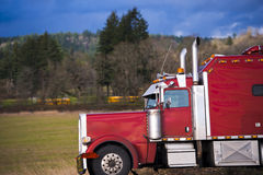 Bright red classic big rig semi trick side view Royalty Free Stock Photo