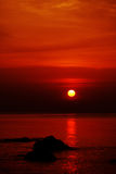 Bright red colored sunset. Under calm smooth sea with stone on front stock photos
