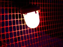 Bright red construction lamp in the mesh background. stock photo