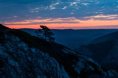 Bright red dawn in the mountains in a windy, cloudy morning, the sun rises from the horizon stock photo