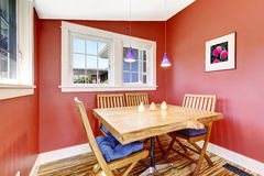 Bright red dining area with rustic table set Stock Images
