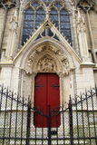 Bright red doors in beautiful stone,with locked gates in front,Notre Dame Cathedral,Paris,France,2016 Royalty Free Stock Image