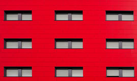 ,Bright red facade of a modern residential building with gray shutters stock images