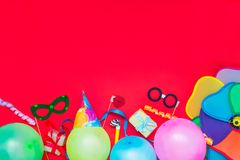 Bright red Festive background with party tools and decoration - baloons, funny carnival masks, festive tinsel. Happy birthday gree. Ting card. Design concept stock images