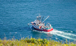 Bright red fishing boat heads out to sea from St. John's harbor Newfoundland, Canada. Stock Images