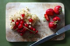 Bright Red Fresh Summer Fruits on Wooden Chopping Board. Strawberries and Currants on Cutting Board with Knife. Green background stock photos