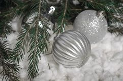 Bright Christmas balls, branches of a Christmas tree in the snow Stock Image
