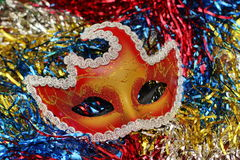 Bright red - gold mask on the background of multi-colored Christmas-tree tinsel Royalty Free Stock Photo