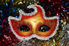 Bright red - gold mask on the background of multi-colored Christmas-tree tinsel Royalty Free Stock Photos