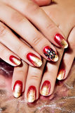 Bright Red and Gold Polish on Nails Stock Photos