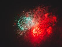Bright holiday fireworks in the dark sky. Bright red green holiday fireworks glow in the dark sky Stock Photography