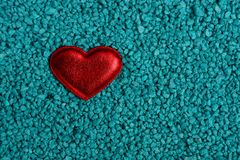 A small red heart rests on small blue stones. Bright red heart on blue sand Royalty Free Stock Image