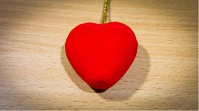 The bright red heart pendant-6 lays on a wooden background. stock photo