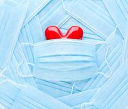 Bright red heart on a pile of medical face masks. Concept of support, love, care and a thank you to the frontline essential