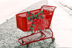 Bright red holiday shopping cart with two bows o the side. Bright red holiday shopping cart with two bows on desaturated background stock images