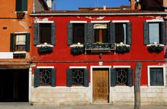 Bright red house with flowers in Burano in the municipality of Venice in Italy Royalty Free Stock Images