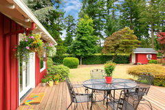 Bright red house with walkout deck and patio area. Beautiful bright red house with patio area on walkout deck and small red shed on backyard stock photography