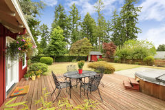 Bright red house with walkout deck and patio area. Beautiful bright red house with patio area on walkout deck and small red shed on backyard royalty free stock photo