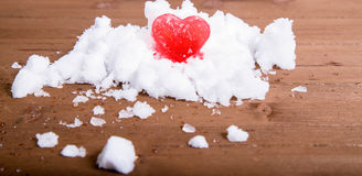 Bright red ice heart on a hill of white snow Royalty Free Stock Photo
