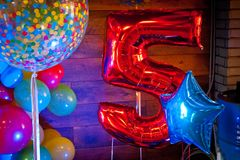 Bright red inflatable balloon next to other balloons with the number five royalty free stock image