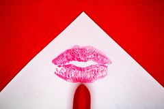 Kiss mark and the red lipstick on the white paper with the red background - Image royalty free stock photography
