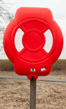 Bright red lifebuoy case on wooden pole. Stands on the beach Royalty Free Stock Photo