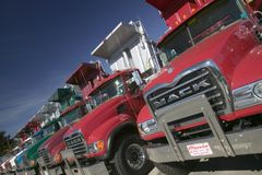 Bright red Mack dump trucks line the road in a row, in Maine near the New Hampshire border Stock Photos