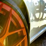 Bright red mag wheel of a white car at sunny day. Exterior of a white car with bright red mag wheel. The glassy surface of the rim and car light gleams on this royalty free stock photography