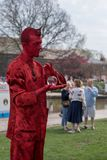 Bright red male living statue rolls glass ball in palm of hand Stock Photo