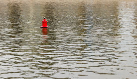 Bright red metal buoy float mark for ships on the smooth spring royalty free stock photography