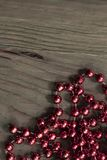 Bright red metallic beads on rustic wood surface stock photos