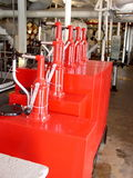 Bright Red Oilers. Freshly painted oilers, used to manually pump oil, sit on the engine room deck of a steamship. Machinery visible in background, slight tilt of royalty free stock photography