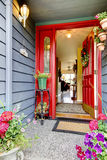 Bright red open front door to blue house with hardwood floor int Royalty Free Stock Image