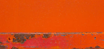 Bright red painted metal background. Painted metal background in bright oranges and reds with blacks, and a rough, peeling texture Royalty Free Stock Image