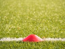 Bright red plastic cone on painted white line of soccer field. Plastic football green turf playground Stock Photos