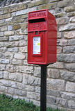 Bright Red Postbox - UK. UK postbox as found in English rural villages. This example on a black pole, and with a limestone wall as backdrop Royalty Free Stock Image