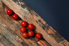 Bright red ripe tomatoes on branch covered with water drops composed on wood planks.  stock photo